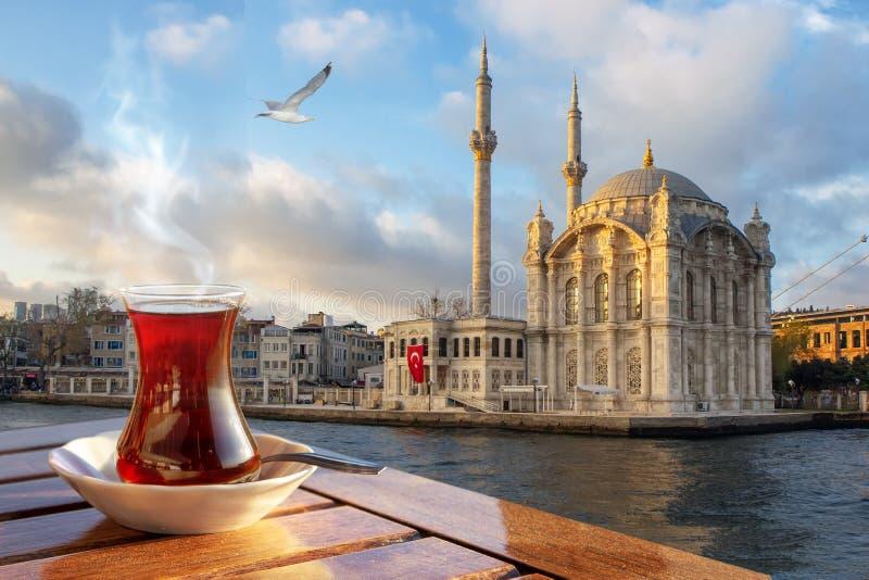 Ένα φλυτζάνι του τουρκικού τσαγιού σε ένα παραδοσιακό γυαλί στα πλαίσια του μουσουλμανικού τεμένους Medgidiye στη Ιστανμπούλ στοκ φωτογραφία με δικαίωμα ελεύθερης χρήσης