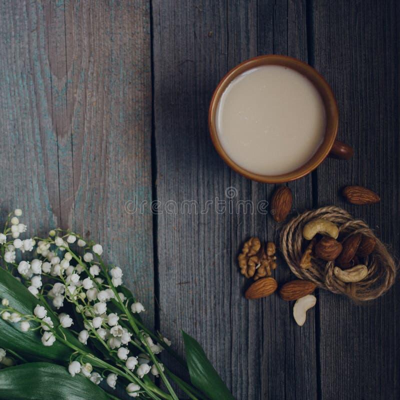 ένα φλυτζάνι του τσαγιού, καρύδια, ανθοδέσμη των κρίνων σε έναν ξύλινο πίνακα στοκ εικόνα με δικαίωμα ελεύθερης χρήσης