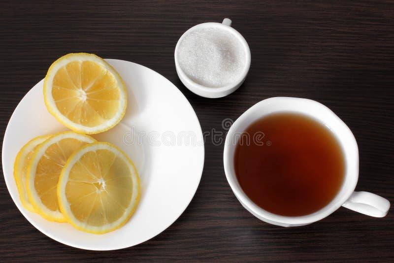 Ένα φλυτζάνι του τσαγιού, λεμόνι σε ένα πιάτο, ζάχαρη σε έναν ξύλινο πίνακα στοκ φωτογραφία με δικαίωμα ελεύθερης χρήσης