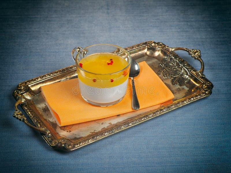 Ένα φλυτζάνι του cotta panna με την πορτοκαλιά ζελατίνα και ρόδινα peppercorns στοκ φωτογραφίες