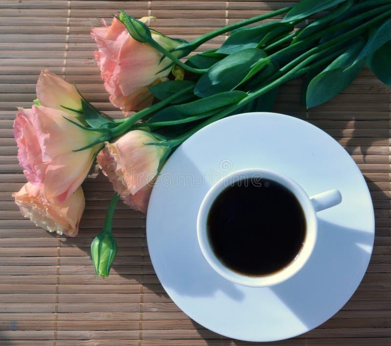 Ένα φλιτζάνι του καφέ με τα ροδαλά λουλούδια στο υπόβαθρο μπαμπού στοκ εικόνες με δικαίωμα ελεύθερης χρήσης
