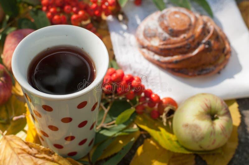 Ένα φλυτζάνι του ισχυρού μαύρου τσαγιού, γλυκό κουλούρι με τις σταφίδες, τα μούρα τέφρας, τα μήλα και τα ζωηρόχρωμα φύλλα φθινοπώ στοκ εικόνα με δικαίωμα ελεύθερης χρήσης