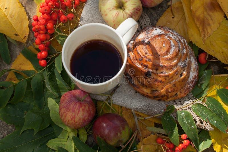 Ένα φλυτζάνι του ισχυρού μαύρου τσαγιού, γλυκό κουλούρι με τις σταφίδες, τα μούρα τέφρας, τα μήλα και τα ζωηρόχρωμα φύλλα φθινοπώ στοκ φωτογραφίες με δικαίωμα ελεύθερης χρήσης