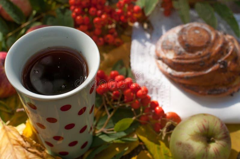 Ένα φλυτζάνι του ισχυρού μαύρου τσαγιού, γλυκό κουλούρι με τις σταφίδες, τα μούρα τέφρας, τα μήλα και τα ζωηρόχρωμα φύλλα φθινοπώ στοκ φωτογραφία
