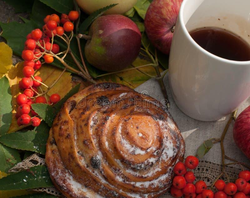 Ένα φλυτζάνι του ισχυρού μαύρου τσαγιού, γλυκό κουλούρι με τις σταφίδες, τα μούρα τέφρας, τα μήλα και τα ζωηρόχρωμα φύλλα φθινοπώ στοκ εικόνες