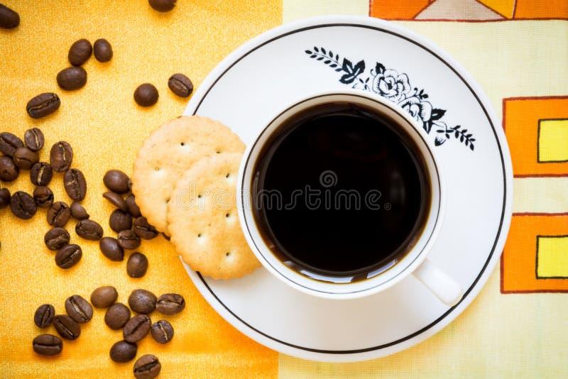 Ένα φλυτζάνι του μαύρων καφέ, των κροτίδων και των φασολιών καφέ στοκ εικόνες με δικαίωμα ελεύθερης χρήσης