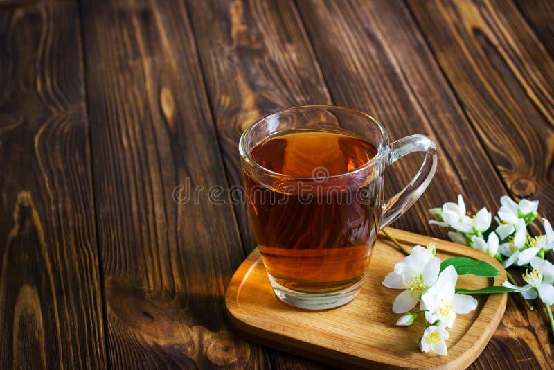 Ένα φλυτζάνι του τσαγιού με jasmine ανθίζει στο καφετί ξύλινο υπόβαθρο στοκ φωτογραφίες