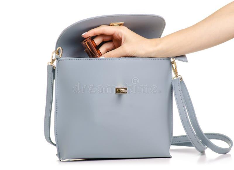 Ένα χέρι έβαλε το καλλυντικό χείλι κραγιόν σχολιάζει στη θηλυκή μπλε γκρίζα τσάντα δέρματος στοκ φωτογραφία με δικαίωμα ελεύθερης χρήσης