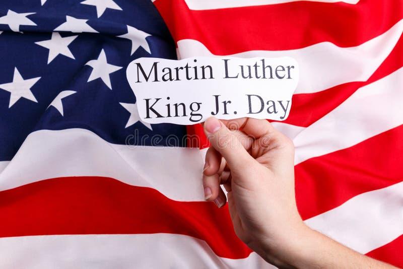 Ένα χέρι ατόμων ` s κρατά ένα έγγραφο με την επιγραφή Martin Luther King Jr Ημέρα, στα πλαίσια της αμερικανικής σημαίας στοκ εικόνα με δικαίωμα ελεύθερης χρήσης