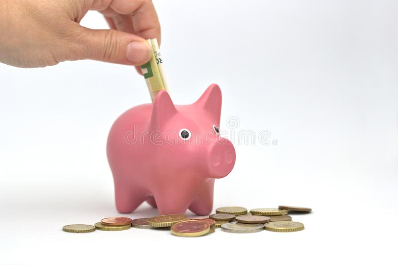 Ένα χέρι βάζει έναν λογαριασμό σε μια piggy τράπεζα στοκ φωτογραφία