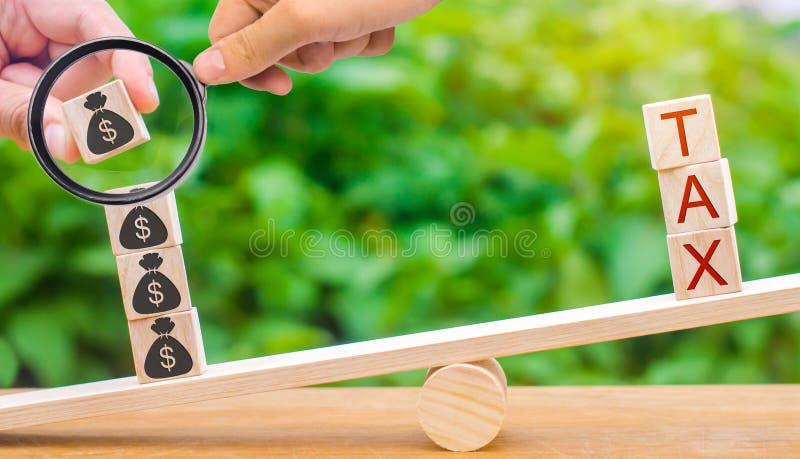Ένα χέρι βάζει τους ξύλινους φραγμούς με τα δολάρια στις κλίμακες και το φόρο λέξης Έννοια της επιτυχούς φορολογικής πληρωμής m Κ στοκ φωτογραφίες