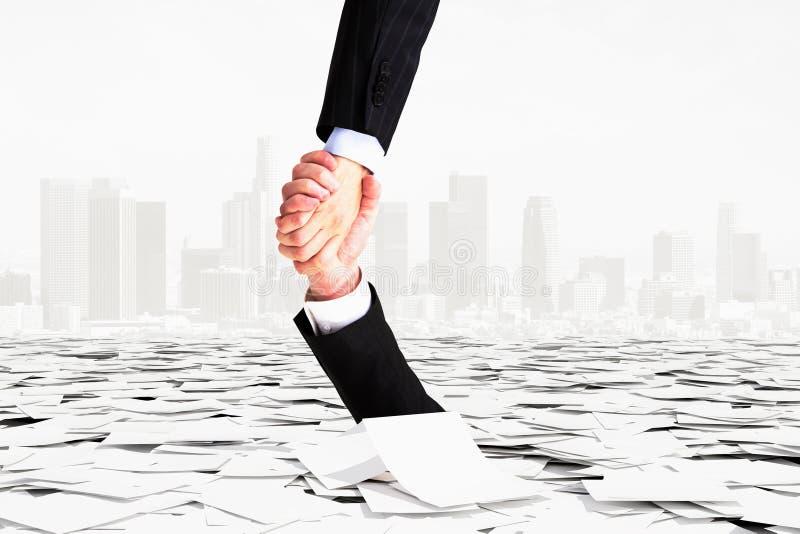 Ένα χέρι βοηθά άλλου για να μην πάει κάτω στη γραφειοκρατία στοκ φωτογραφία