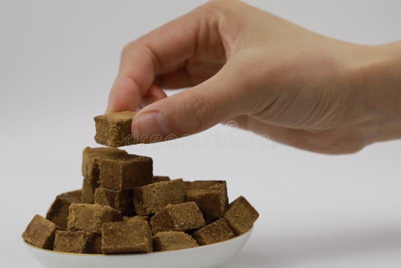 Ένα χέρι γυναικών κρατά ένα κομμάτι της καφετιάς ζάχαρης, ζάχαρη βράχου κύβων σε ένα πιάτο, στο άσπρο υπόβαθρο, διαβήτης στοκ εικόνα