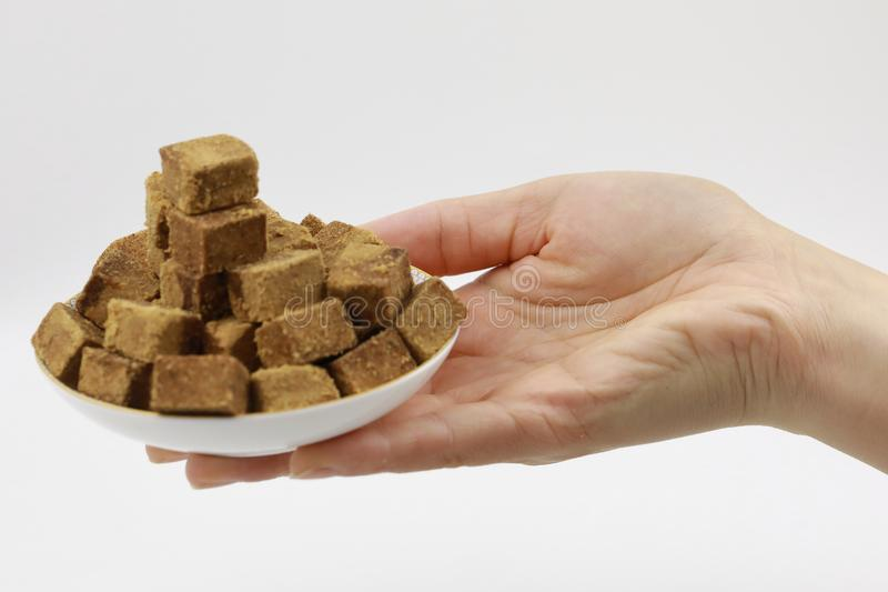 Ένα χέρι γυναικών κρατά ένα πιάτο της καφετιάς ζάχαρης, ζάχαρη βράχου κύβων σε ένα πιάτο, στο άσπρο υπόβαθρο, διαβήτης στοκ εικόνα