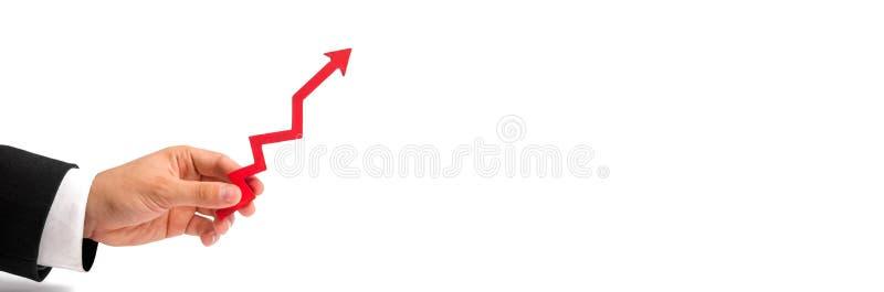 Ένα χέρι επιχειρηματιών ` s κρατά ένα κόκκινο βέλος επάνω σε ένα άσπρο υπόβαθρο Η έννοια της αύξησης και του πολλαπλασιασμού του  στοκ φωτογραφία με δικαίωμα ελεύθερης χρήσης