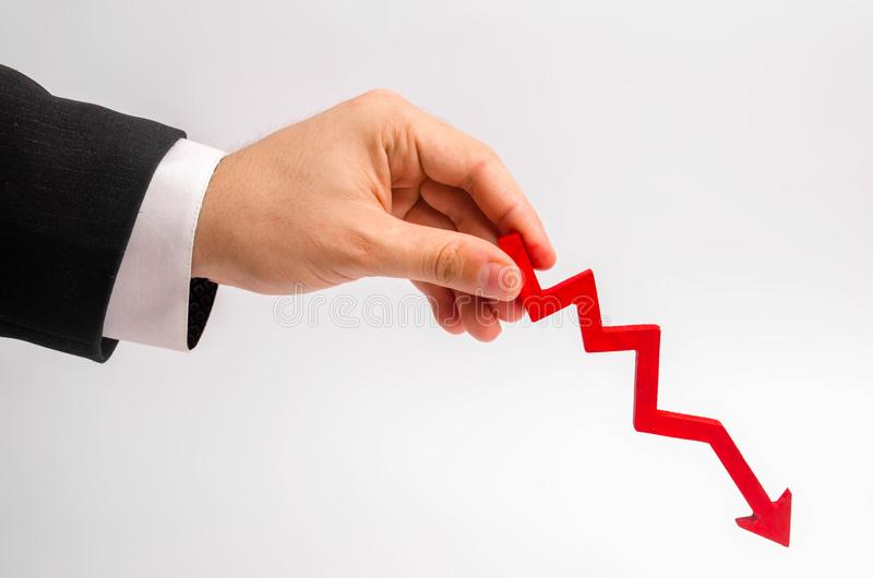 Ένα χέρι επιχειρηματιών ` s κρατά ένα κόκκινο βέλος κάτω σε ένα άσπρο υπόβαθρο Η έννοια της μείωσης των δαπανών και των κερδών, μ στοκ φωτογραφία