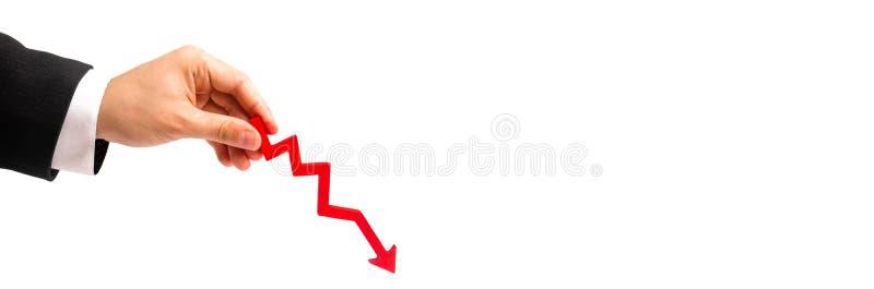 Ένα χέρι επιχειρηματιών ` s κρατά ένα κόκκινο βέλος κάτω σε ένα άσπρο υπόβαθρο έννοια της μείωσης των δαπανών και των κερδών, μει στοκ φωτογραφία με δικαίωμα ελεύθερης χρήσης