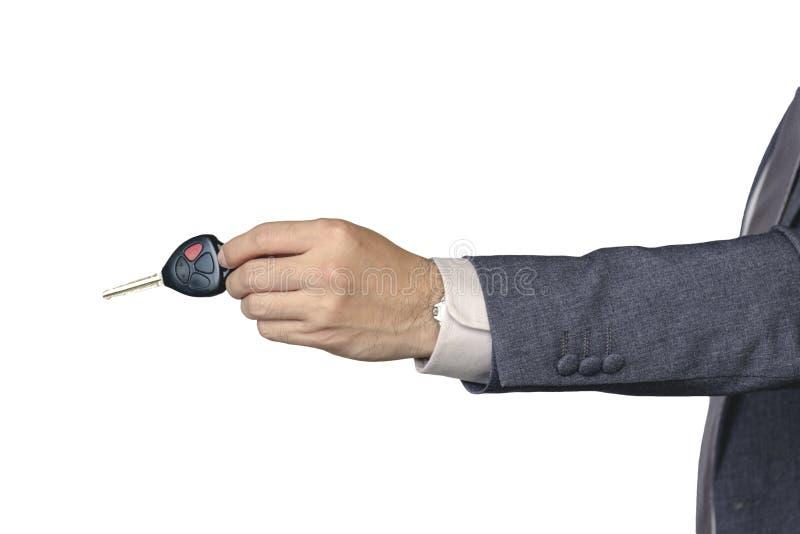 Ένα χέρι επιχειρηματιών ` s στέλνει ένα κλειδί αυτοκινήτων στο χέρι του σε ένα απομονωμένο άσπρο υπόβαθρο στοκ φωτογραφία με δικαίωμα ελεύθερης χρήσης