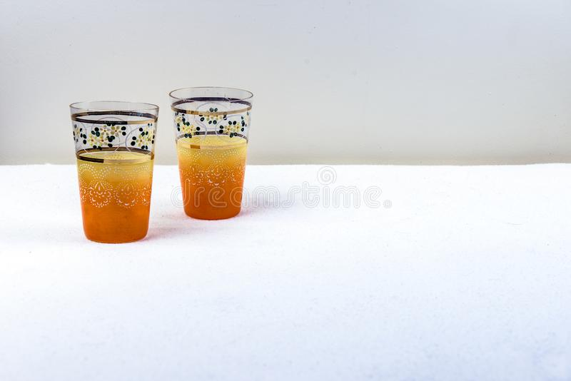 Ένα χέρι ζευγαριού επεξεργάστηκε τα κίτρινα πορτοκαλιά εκλεκτής ποιότητας γυαλιά κατανάλωσης στοκ φωτογραφίες με δικαίωμα ελεύθερης χρήσης