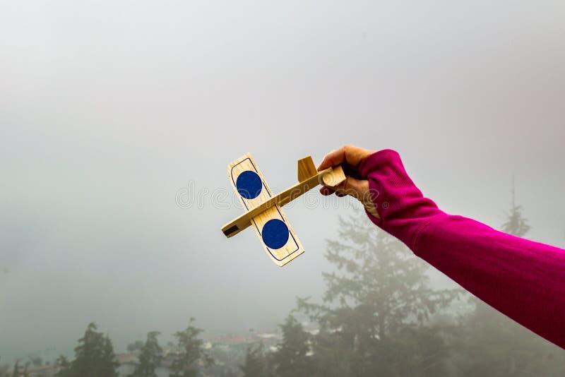 Ένα χέρι κρατά ένα ξύλινο, αεροπλάνο παιχνιδιών έτοιμο να πετάξει μια misty ημέρα σε Astoria, Όρεγκον στοκ εικόνες