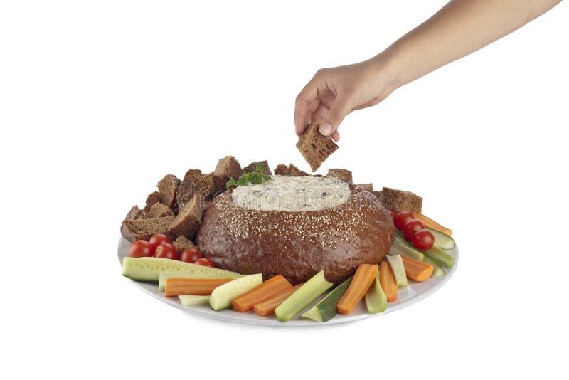 Ένα χέρι με έναν κύβο ψωμιού περίπου που βυθίζει στην εμβύθιση σπανακιού στοκ φωτογραφία με δικαίωμα ελεύθερης χρήσης