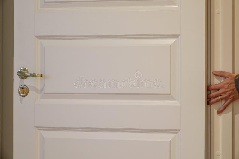 Ένα χέρι περίπου που παίρνει καταπληκτικό σε μια πόρτα στοκ φωτογραφία με δικαίωμα ελεύθερης χρήσης