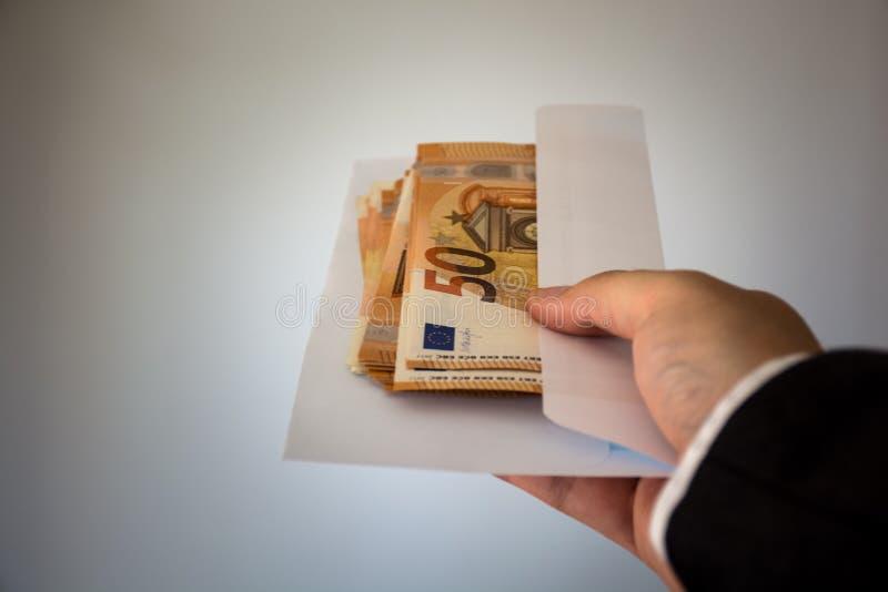 Ένα χέρι που δίνει ένα σύνολο φακέλων των χρημάτων, 50 ευρο- σημειώσεις στοκ εικόνα