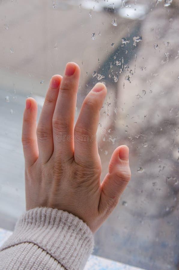 Ένα χέρι σε ένα βροχερό παράθυρο στοκ φωτογραφία με δικαίωμα ελεύθερης χρήσης
