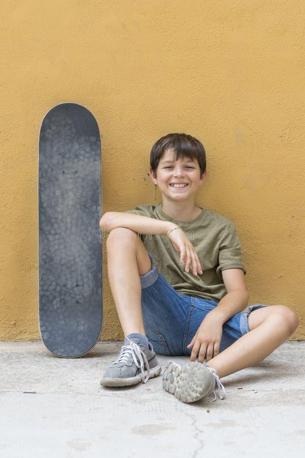 Ένα χαμογελώντας αγόρι με skateboard τη συνεδρίαση μόνο στοκ φωτογραφία με δικαίωμα ελεύθερης χρήσης