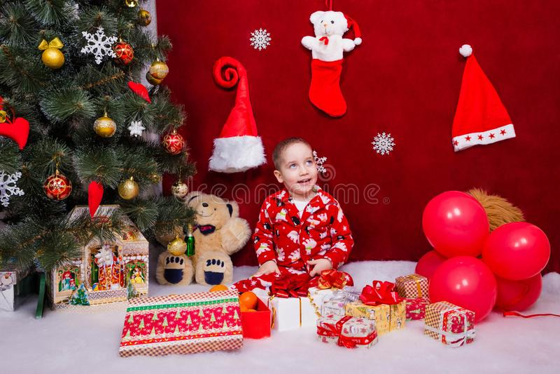 Ένα χαμογελώντας παιδί κάθεται με πολλά χριστουγεννιάτικα δώρα στοκ εικόνες