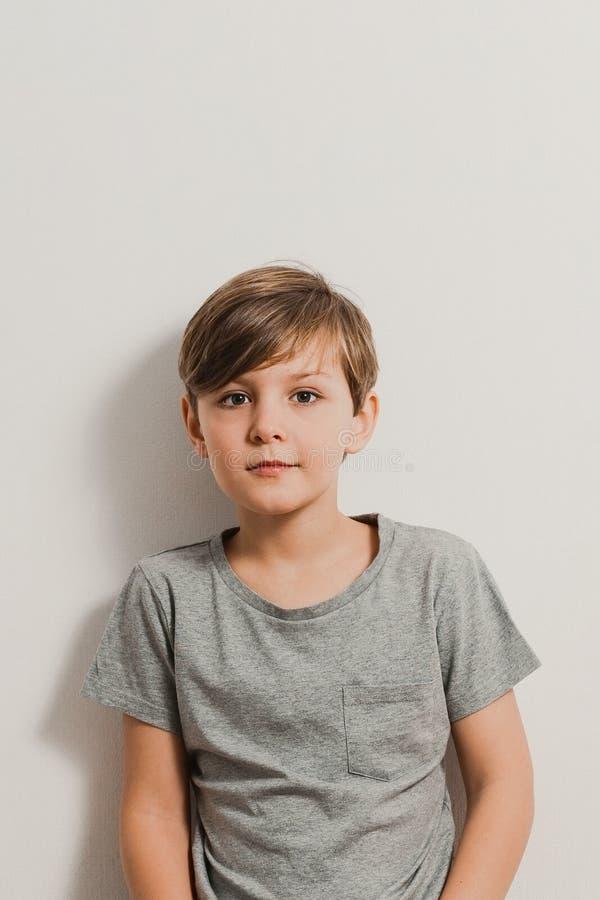 Ένα χαριτωμένο αγόρι που στέκεται δίπλα στον άσπρο τοίχο, γκρίζο πουκάμισο, χαμόγελο στοκ φωτογραφίες