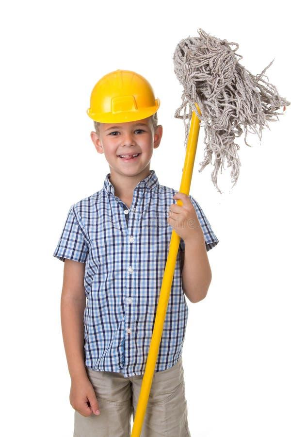Ένα χαριτωμένο αγόρι σε ένα κίτρινο κράνος με μια σφουγγαρίστρα αρωγός λίγα στοκ φωτογραφία με δικαίωμα ελεύθερης χρήσης