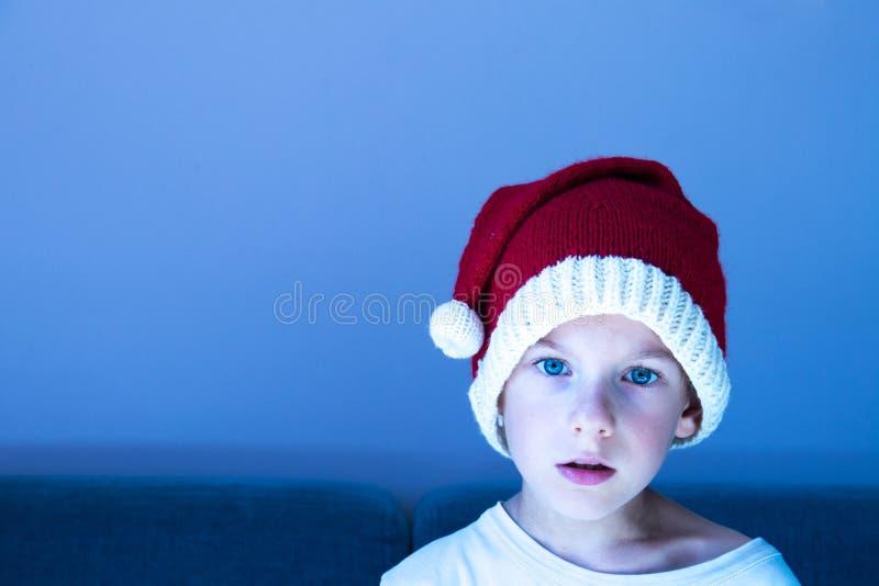 Ένα χαριτωμένο απομονωμένο παιδί που φορά ένα πλεκτό καπέλο Santa Σχέδιο Χριστουγέννων στοκ εικόνα με δικαίωμα ελεύθερης χρήσης