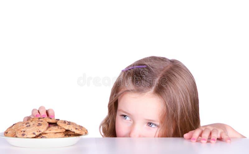 Ένα χαριτωμένο κορίτσι κλέβει τα μπισκότα στοκ εικόνα με δικαίωμα ελεύθερης χρήσης