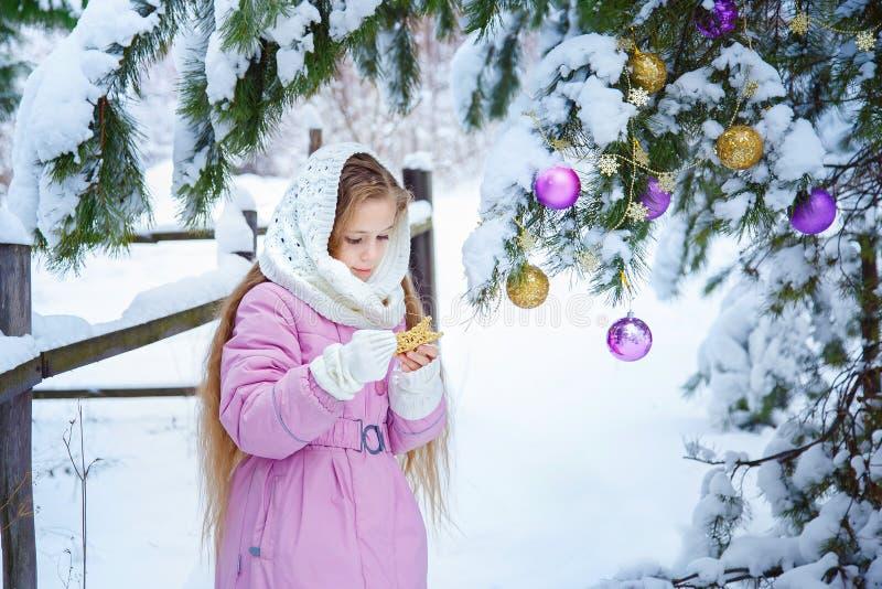 Ένα χαριτωμένο μικρό κορίτσι σε ένα ρόδινο παλτό και ένα άσπρο μαντίλι εξωραΐζει το Chris στοκ φωτογραφίες