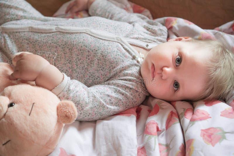 Ένα χαριτωμένο μικρό μωρό είναι ξύπνησε και βρίσκεται στο κρεβάτι, ηρεμία και κατευνασμένος στοκ εικόνα με δικαίωμα ελεύθερης χρήσης