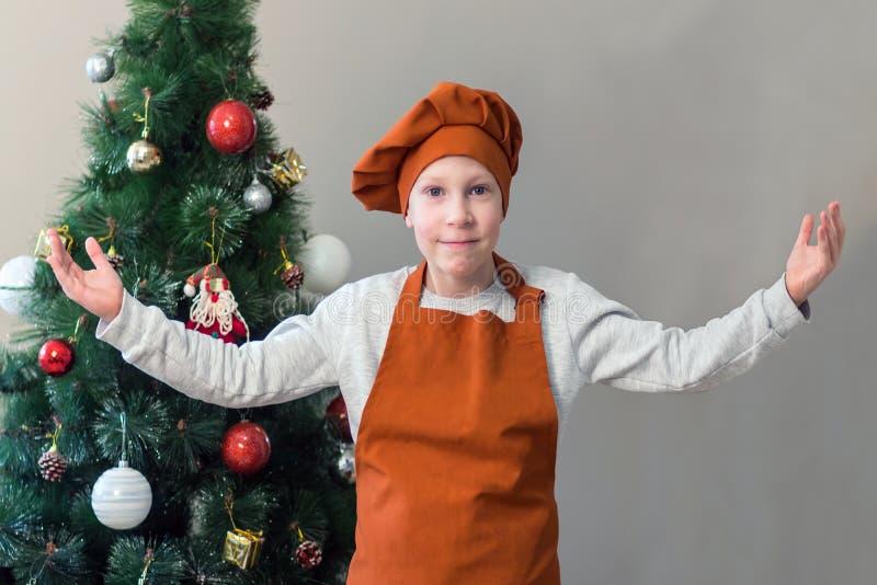 Ένα χαριτωμένο νέο αγόρι χαμόγελου στην πορτοκαλιά μορφή ενός μάγειρα αύξησε τα χέρια του προσκαλώντας το καθένα στο νέο πίνακα έ στοκ εικόνες με δικαίωμα ελεύθερης χρήσης