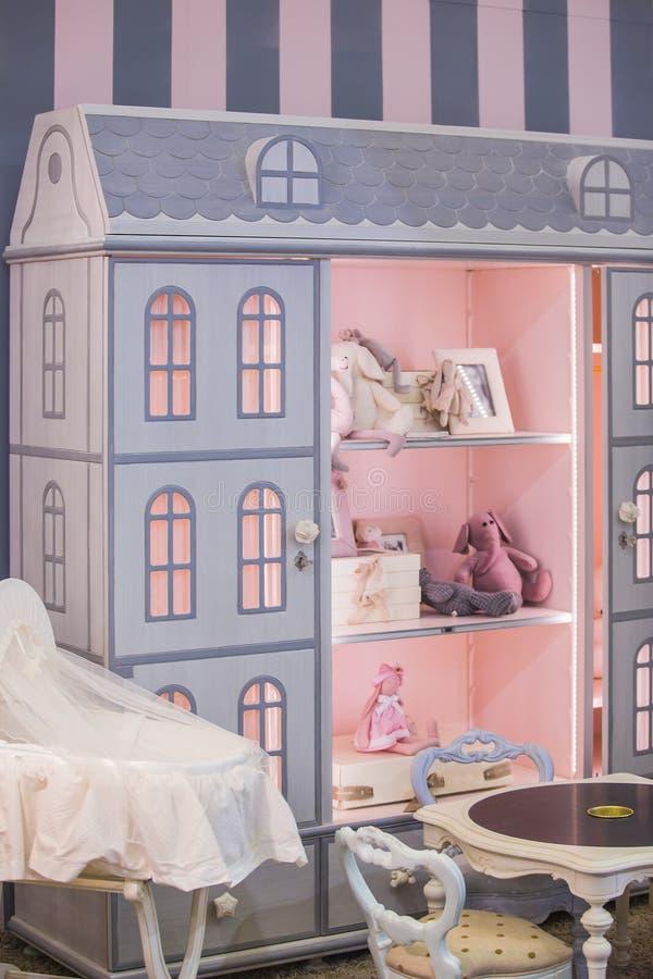 Ένα χαριτωμένο ντουλάπι κοριτσιών ` s παιδιών ` s με τα ράφια υπό μορφή σπιτιού κουκλών ` s Εσωτερικό ενός δωματίου παιδιών ` s γ στοκ φωτογραφίες