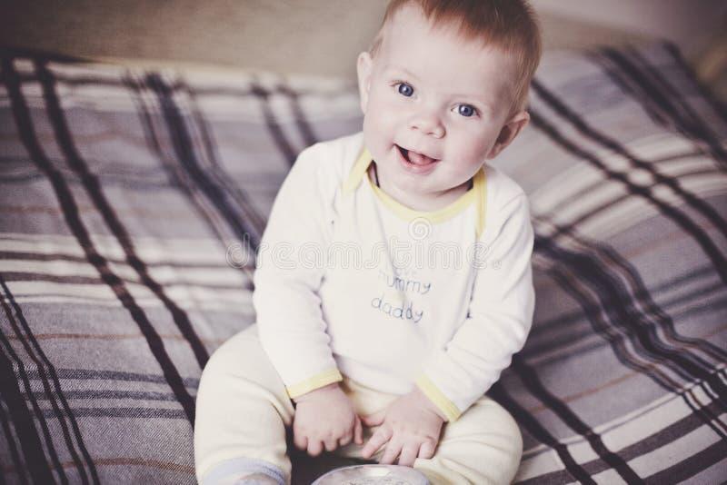 Ένα χαριτωμένο ξανθό μωρό στα ελαφριά ενδύματα κάθεται σε ένα κάλυμμα καρό στο κρεβάτι και χαμογελά στοκ εικόνες