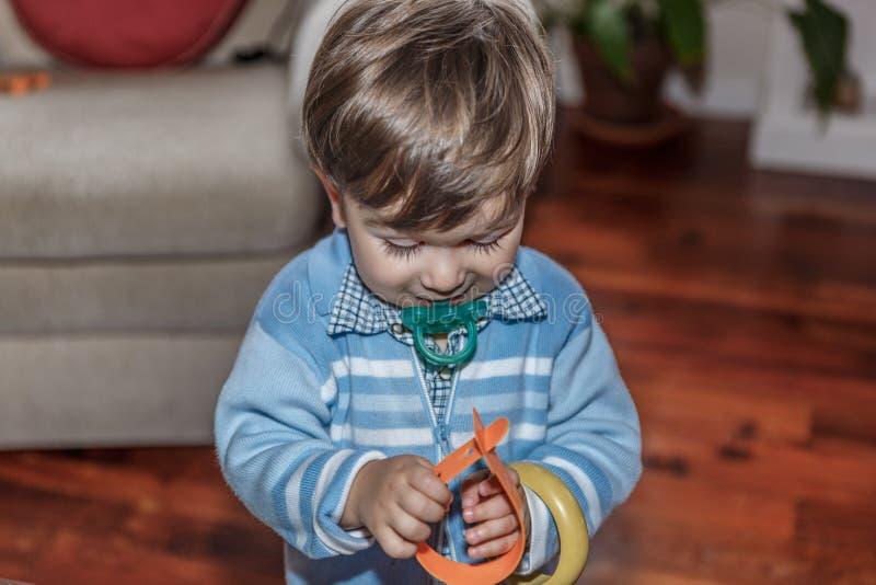 Ένα χαριτωμένο ξανθό παιδί με έναν ειρηνιστή παίζει με μερικά βραχιόλια στο καθιστικό στοκ εικόνες με δικαίωμα ελεύθερης χρήσης