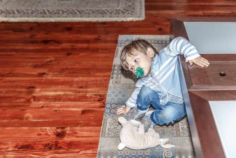 Ένα χαριτωμένο ξανθό παιδί με έναν ειρηνιστή παίζει στο καθιστικό στοκ φωτογραφία
