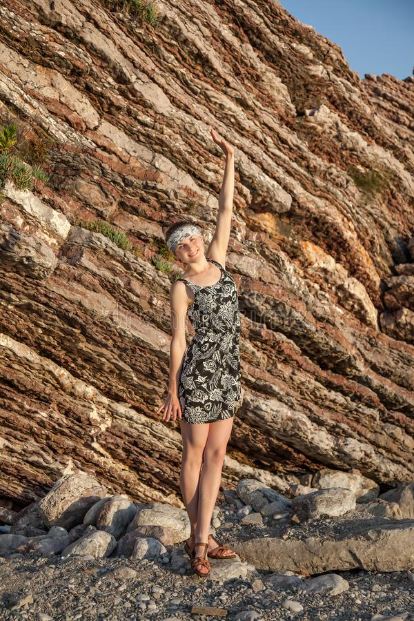 Ένα χαρούμενο λεπτό κορίτσι σε ένα φόρεμα στέκεται στους παράκτιους απότομους βράχους στοκ εικόνες
