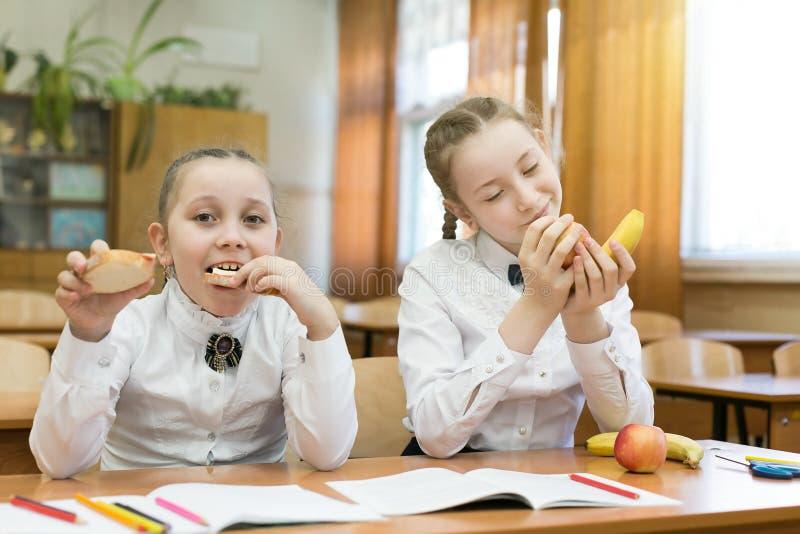Ένα χορτοφάγο κορίτσι εξετάζει τα τρόφιμα του φίλου της με το φθόνο στοκ εικόνες