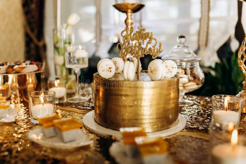 Ένα χρυσό κέικ γενεθλίων είναι διακοσμημένο με τα μακαρόνια στοκ εικόνες με δικαίωμα ελεύθερης χρήσης