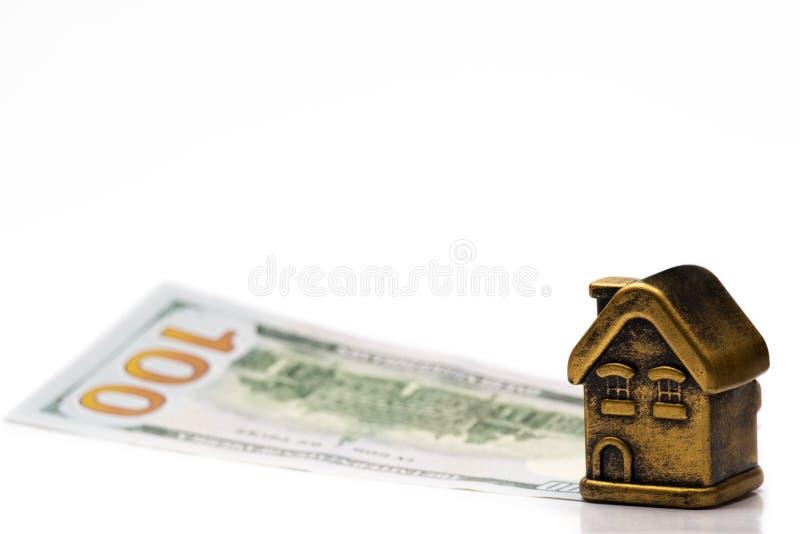 Ένα χρυσό σπίτι παιχνιδιών στέκεται σε έναν λογαριασμό 100 αμερικανικών δολαρίων Υποθήκη έννοιας, δάνειο, υποχρέωση, οικονομική ε στοκ εικόνες με δικαίωμα ελεύθερης χρήσης