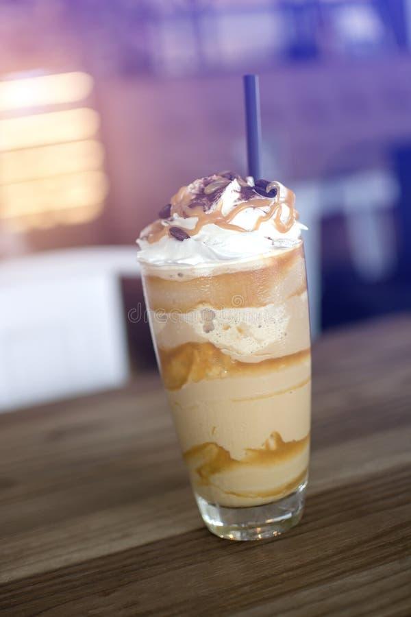 Ένα ψηλό γυαλί παγωμένος frappe, με το κτυπημένο σιρόπι κρέμας και καραμέλας, με τα άχυρα και τα σιτάρια του καφέ στον ξύλινο πίν στοκ εικόνα