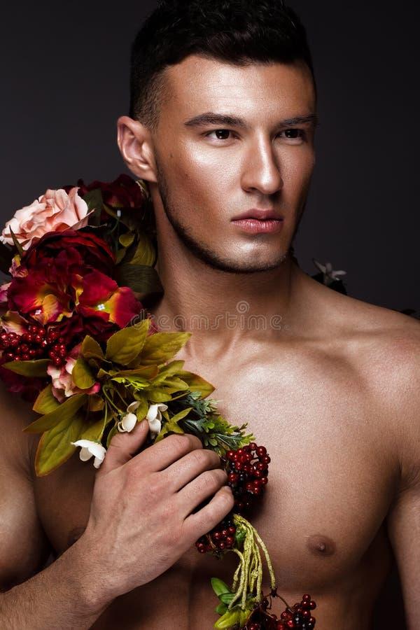 Ένα όμορφο άτομο με έναν γυμνό κορμό, ένα μαύρισμα χαλκού και τα λουλούδια στο σώμα του στοκ εικόνα