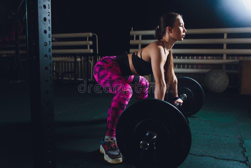 Ένα όμορφο αθλητικό κορίτσι εκπαιδεύει ένα bicep με μια ράβδο σε την παρα στοκ φωτογραφία
