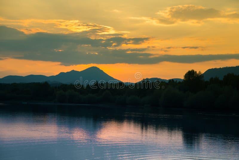 Ένα όμορφο, ζωηρόχρωμο τοπίο ηλιοβασιλέματος με τη λίμνη, βουνό και δασικό φυσικό τοπίο βραδιού πέρα από τη λίμνη βουνών το καλοκ στοκ φωτογραφία με δικαίωμα ελεύθερης χρήσης