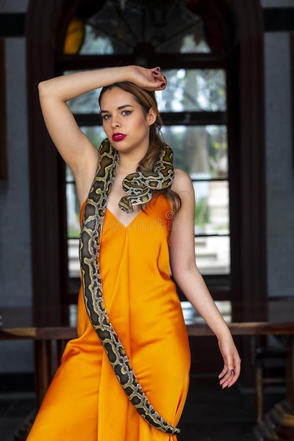 Ένα όμορφο ισπανικό πρότυπο Brunette θέτει με ένα Boa φίδι σφιγκτήρων γύρω από το σώμα της στοκ φωτογραφία